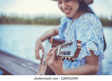 Young cute hipster girl playing a classical guitar. Filtered image.