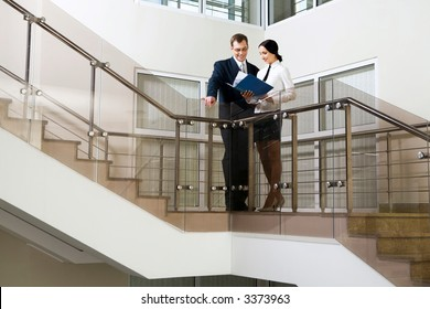 Young cute Hispanic businesswoman showing documents to her colleague on stairs in the office building