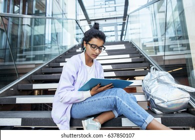 young cute indian girl at university building sitting on stairs reading a book, wearing hipster glasses, lifestyle people concept