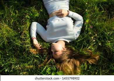 Young cute lady lying on the green grass, shot from above.