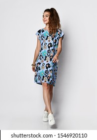 Young cute long-haired woman posing in a new floral blue pattern fashion dress in sneakers happy full body smiles on a white background