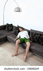 Young cute male falling asleep while watching TV