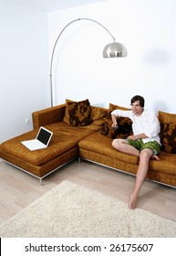 Young cute male relaxing on couch watching TV