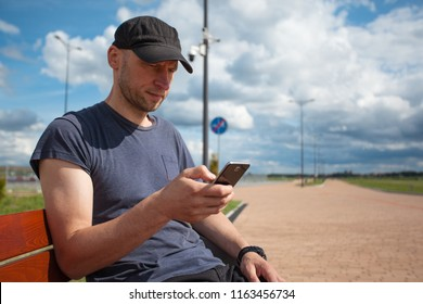 young cute man with a bristle on an outdoor bench with a smartphone