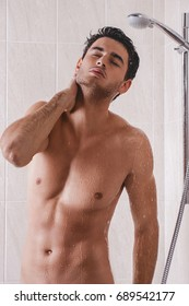 Young cute man washing head in bathroom