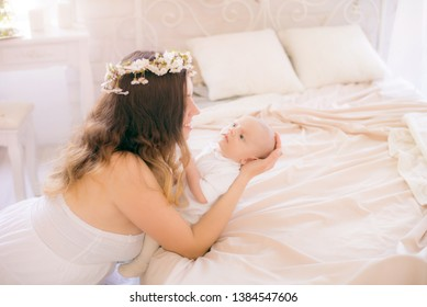 Young cute mom in a wreath of cherry blossoms in a white dress holding a baby in her arms in a spring bedroom with blossoming cherry branches
