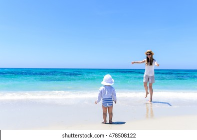 Young cute mother in sunglasses, shorts, T-shirt and straw hat and her adorable little daughter in swimsuit having fun at white tropical sandy beach over background of turquoise sea during vacation