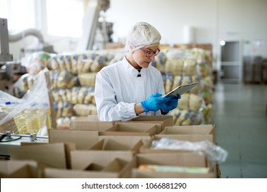 Young cute professional female worker in sterile cloths is using a tablet inside a factory storage room while being leaned against boxes.