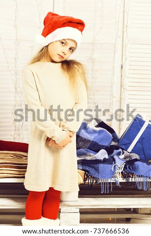 8fcdf69040 young cute serious blonde girl in christmas red hat and footless tights in  beige dress stand