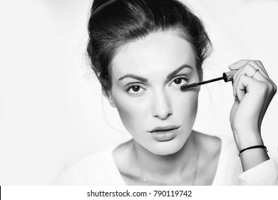 young cute sexy woman or girl portrait with pretty face and brunette hair dyeing eyelashes with mascara brush as fashionable makeup in white shirt