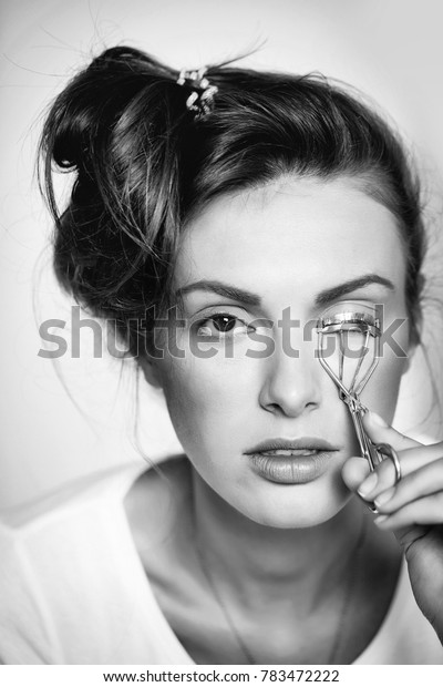 young cute sexy woman or girl portrait with pretty face and brunette hair curling eyelashes with tongs or forceps as fashionable makeup on white background