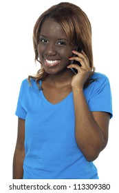 Young cute smiling african girl talking through cellphone isolated against white background