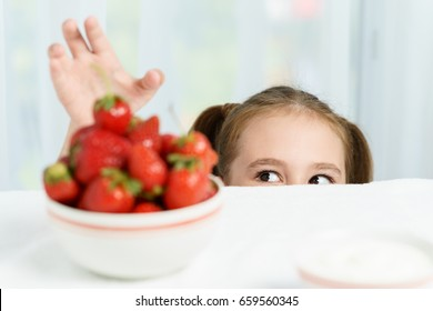 Young cute smiling european little girl is trying to steal ripe jucy strawberry from plate of many berries while she sitting under white table