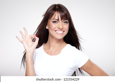 Young cute smiling girl showing OK sign on gray