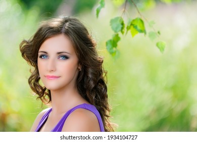 Young cute smiling woman with long dark curly hair in a purple dress on the background of a summer green park.