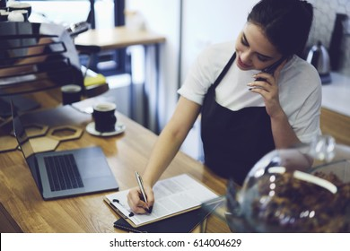 Young cute student working waitress in coffee shop after lessons.Caucasian hipster girl talking on cellphone with friends and writing phone number new delivery of delicious cakes in cafeteria