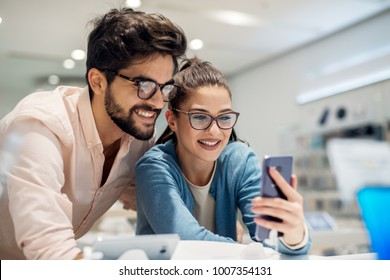Young cute stylish smiling couple testing the new model of a mobile from the desk in the tech store. Multiracial couple, multicultural.