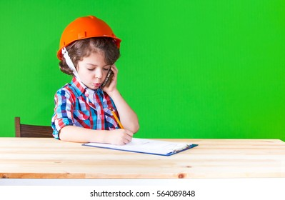 Young cute superintendent in a helmet speaks on the phone, sticking out his lip pencil writing in a notebook. Close-up. Green background.
