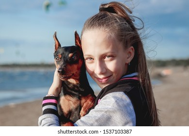 young cute teenage girl with blond ponytail and blue eyes hugs her pet dog black mini pinscher at summer sunny beach