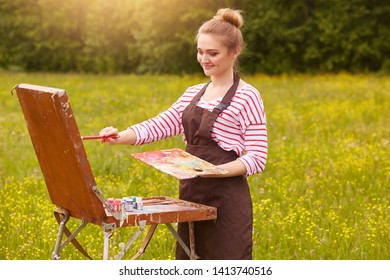 Young cute woman artist finishes painting with pleasant facial expression, posing isolated on meadow background, stands in front of sketchbook, holds palette smeared in paint. Art and creation concept
