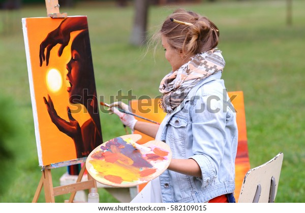 Young cute woman artist  finishes painting which depicts woman who keeps  sun on orange background, sitting with his back to  photographer and  behind wooden easel, holds palette smeared in paint in l