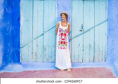 young cute woman with hat and white floral dress, standing in front of a blue door of some blue city of morocco