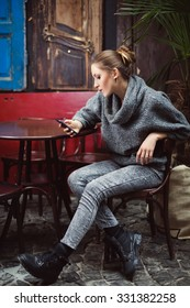 Young cute woman looking in her smartphone sitting in cafe