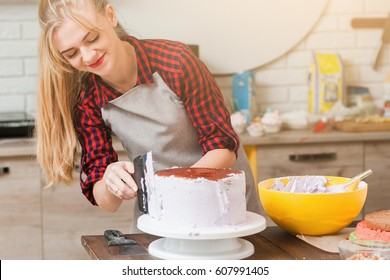 Young cute woman making biscuit cake with white cream on wooden kitchen table. Culinary masterclass of cooking desserts. Blogger preparing colorful festive food