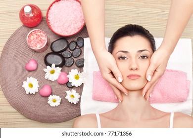 young cute woman receiving a facial massage at spa center