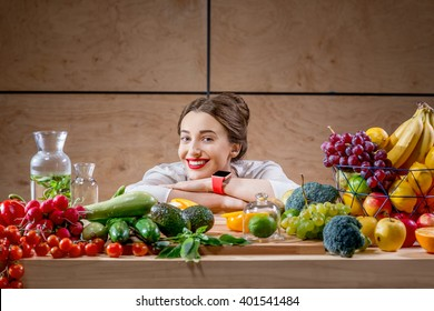 Young and cute woman sitting at the table full of fruits and vegetables in the wooden interior. Healthy food concept. Beauty and wellbeing