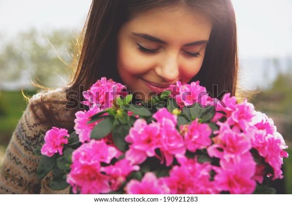 ピンクの花の香りをかぐ若いかわいい女性