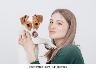 Young cute woman smiles and hugs her small jack russell terrier dog. Love between owner and dog. Isolated on white background. Studio portrait.