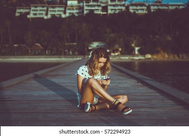Young cute woman using phone,sitting at a cafe holding a smartphone,answering texts,phone calls,letters,posts photos in instagram,outdoor portrait, close up, elaborated and bracelets on the hands pier