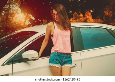 young cutie girl in sunglasses posing at the white car on a sunset in the autumn
