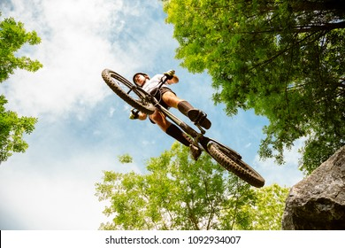 Young cyclist flying with his bycicle from a rock in the forest. Extreme low angle view