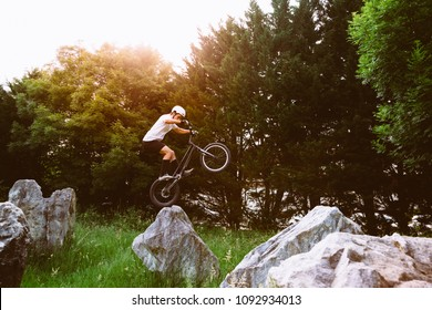 Young cyclist jumping with the rear wheel of a trial bicycle on a rock at sunset.