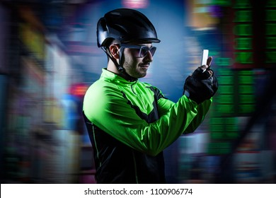 Young cyclist looking smartphone on urban background