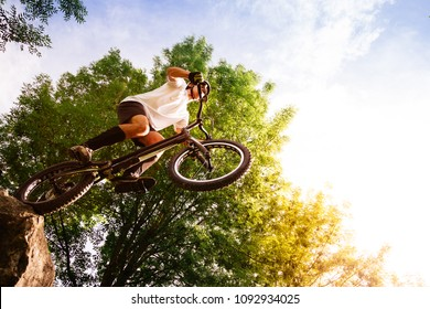 Young cyclist on the edge of a rock about to jump with a trial bicycle. Low angle view