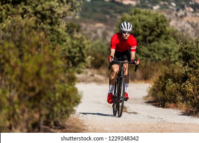 young cyclist with red jersey and black bike rides on a path with his gravel bike