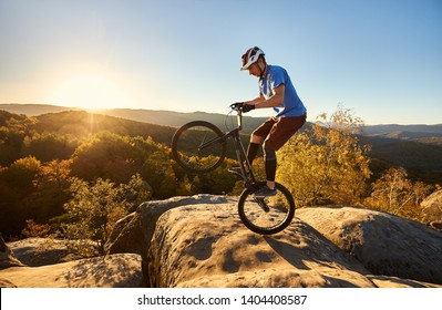Young cyclist standing on back wheel on trial bicycle. Sportsman rider making acrobatic stunt on the edge of big boulder on the top of mountain at sunset. Concept of extreme sport active lifestyle