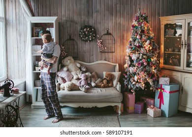 young dad with a baby standing near the Christmas tree