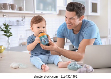 Young dad giving water to his little son at home