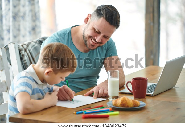 Young dad with green highlighter helping his little son draw a picture on paper while both sitting by table