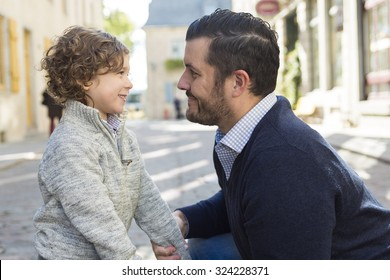 A Young dad with her son ooutside in a urban street