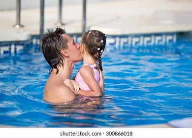 Young dad and little daughter playing in swimming pool enjoying summer vacation