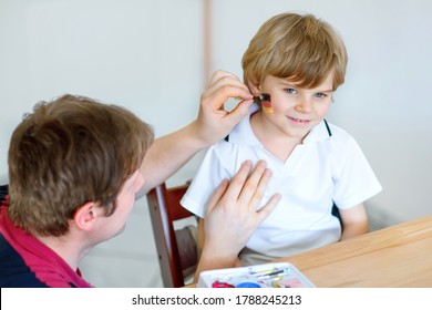Young dad painting flag on face of little son for football or soccer game. Happy excited preschool kid boy fan and father preparing for game of favorite team for watching and cheering on stadion.