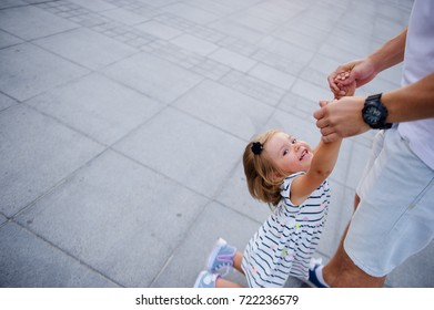 Young dad is playing with a charming little daughter. The man is holding the baby by the handles.. The child rejoices.