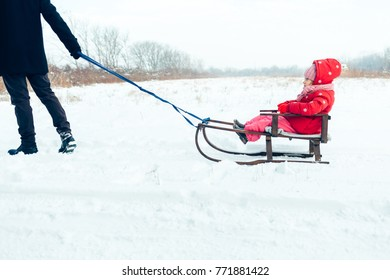 Young dad rolls his child on sledge in winter day