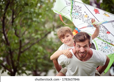 young dad running with son on his back with kite in his hand, having fun
