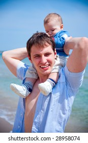 young dad walking along the beach with his son sitting on his shoulders